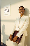 Businesswoman, in white suit, standing outside meeting room with folder, smiling, portrait Royalty Free Stock Images