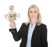 Businesswoman winning a trophy. Isolated on white Royalty Free Stock Photos