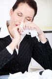 Businesswoman wiping her nose. Royalty Free Stock Photography