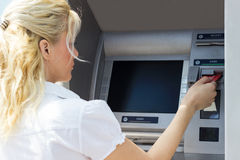 Businesswoman withdrawing money from credit card Stock Image