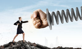 Businesswoman withstanding fist. Young determined businesswoman fighting with fist on spring Royalty Free Stock Images