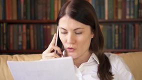 Businesswoman work with documents at home. Professional female talking on cellphone with colleague. Businesswoman in white shirt working with documents at home stock footage