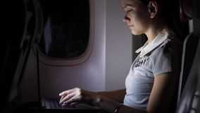 Businesswoman work on notebook in airliner. Girl sitting with laptop in plane stock video