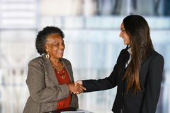 Businesswoman At Work With Senior Client. Confident businesswoman who is working with an elderly client Stock Photo