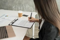 Businesswoman at work signing a contract paper in her workstatio. N Stock Photography