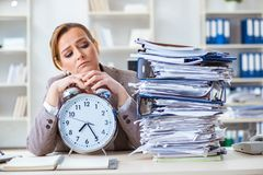 The businesswoman workaholic trying to finish urgent paperwork. Businesswoman workaholic trying to finish urgent paperwork Stock Image