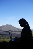 Businesswoman Working. Silhouette of business woman working with a mountain in the background Stock Images