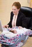 Businesswoman working with baby at desk Stock Photos