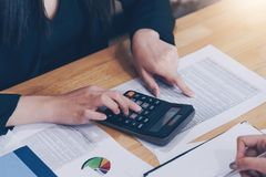 Businesswoman working with calculator for calculate business data at meeting room. Meeting planning budget and cost.  royalty free stock image
