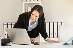 Businesswoman working comparing documents online royalty free stock image