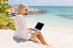 Businesswoman working with computer on the beach Stock Images