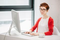 Businesswoman working on computer and looking at camera in office. Portrait of businesswoman wearing glasses working on computer and looking at camera in office Stock Images