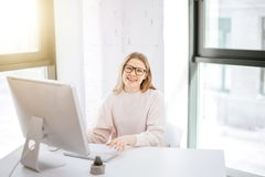 Businesswoman working on computer and looking at camera in office. Portrait of businesswoman wearing glasses working on computer and looking at camera in office Royalty Free Stock Images