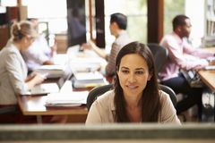 Businesswoman Working At Desk With Meeting In Background Royalty Free Stock Photo