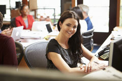 Businesswoman Working At Desk With Meeting In Background Stock Image