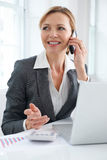 Businesswoman Working At Desk Talking On Mobile Phone Royalty Free Stock Image