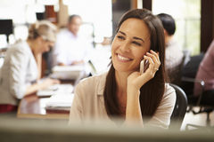 Businesswoman Working At Desk Using Mobile Phone Royalty Free Stock Images