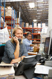 Businesswoman Working At Desk In Warehouse. Smiling royalty free stock image