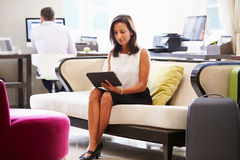 Businesswoman Working On Digital Tablet In Hotel Lobby Stock Photo