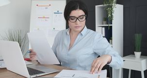 Businesswoman working with documents and laptop at office. Businesswoman doing paperwork and working on laptop at office stock video