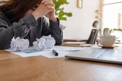 Businesswoman working with feeling frustrated and stressed with screwed up papers and laptop on table in office. A businesswoman working with feeling frustrated stock image