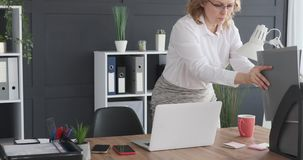 Businesswoman working with filed document and laptop. Businesswoman keeping file and working on laptop at office desk stock footage