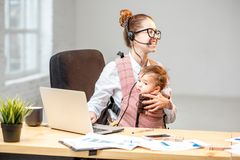 Businesswoman working with her baby son at the office Royalty Free Stock Image