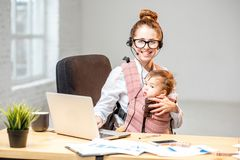 Businesswoman working with her baby son at the office Stock Photos