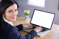 Businesswoman working at her desk on laptop Stock Photos