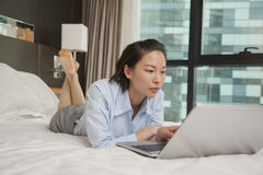 Businesswoman working on her laptop in the bed Royalty Free Stock Image