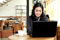 Businesswoman working on her laptop during coffee break Stock Images