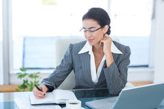 Businesswoman working with her laptop and writing notes Royalty Free Stock Image
