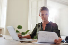 Businesswoman working from home office. Shot of young woman sitting at table with laptop and reading documents. Beautiful businesswoman working from home office royalty free stock photos