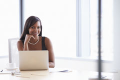 Businesswoman Working On Laptop At Boardroom Table Stock Photo