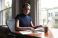 Businesswoman Working On Laptop And Checking Mobile Phone Royalty Free Stock Images