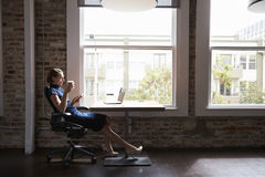 Businesswoman Working On Laptop And Checking Mobile Phone Royalty Free Stock Photography