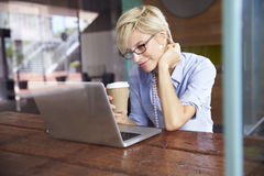 Businesswoman Working On Laptop In Coffee Shop Stock Photography