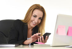 Businesswoman working at laptop computer office desk sending text message on mobile phone Royalty Free Stock Images