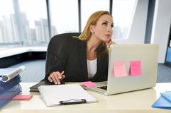 Businesswoman working at laptop computer sitting on the desk absent minded Stock Photography