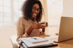 Businesswoman enjoying a cup of coffee while working on laptop a stock photos