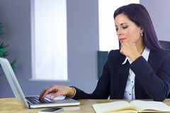 Businesswoman working with laptop at desk Royalty Free Stock Photography