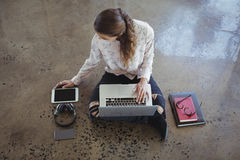 Businesswoman working with laptop and digital tablet on floor Stock Photos