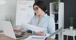 Businesswoman doing paperwork at office desk. Businesswoman working on laptop and doing paperwork at office desk stock footage