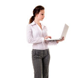 Businesswoman working at a laptop full length isolated on white Stock Photo