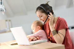 Businesswoman working on laptop with her baby Stock Photography