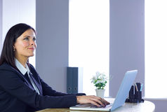 Businesswoman working on laptop at her desk Stock Photo