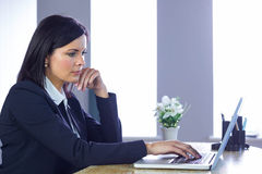 Businesswoman working on laptop at her desk Royalty Free Stock Photo