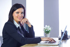 Businesswoman working on laptop at her desk Stock Photos