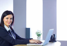 Businesswoman working on laptop at her desk Stock Photography