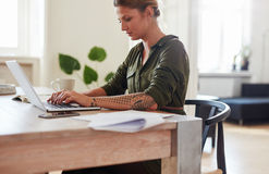 Businesswoman working on laptop at home office Stock Images